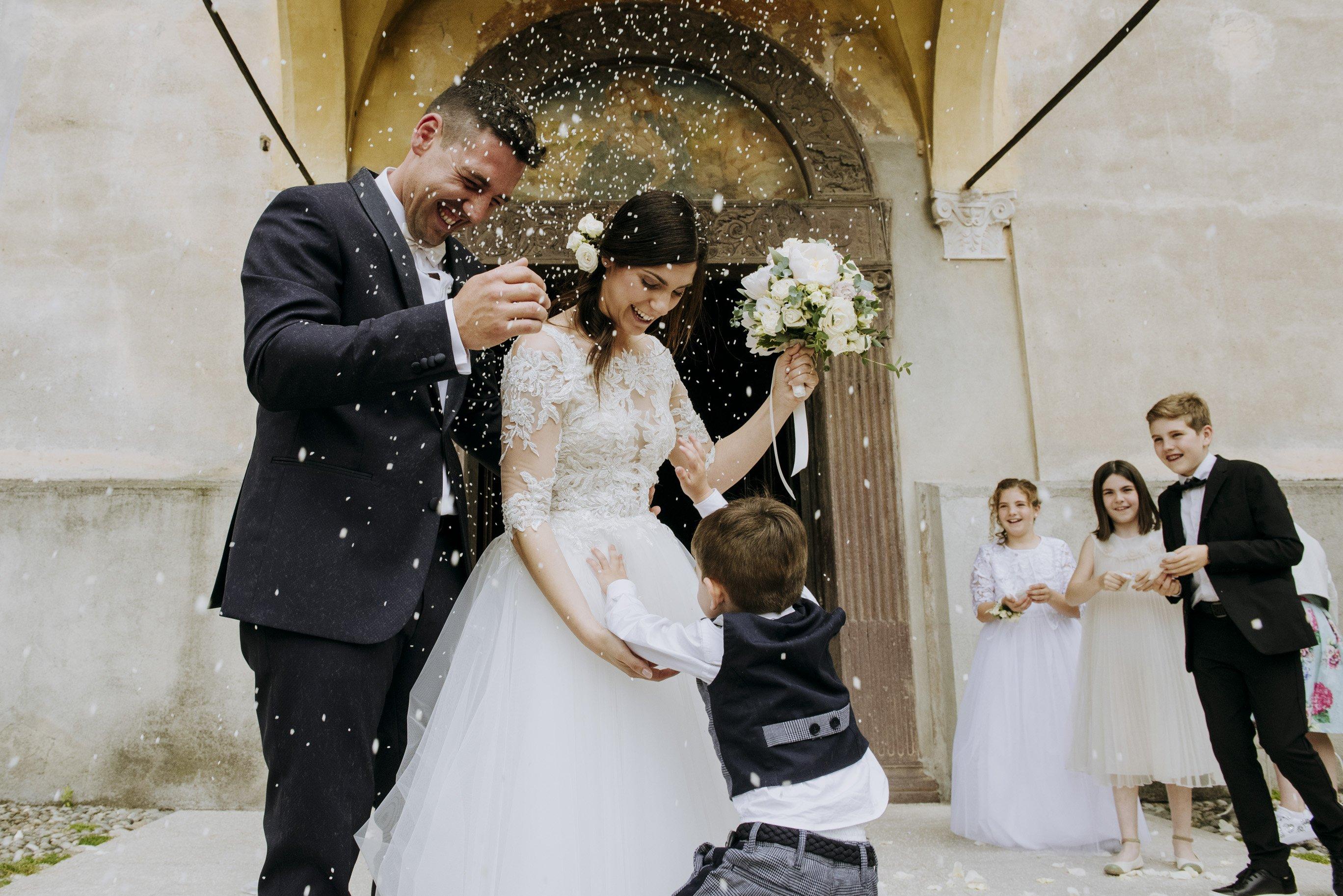 sposi all'uscita dalla chiesa con bambini sposa felice